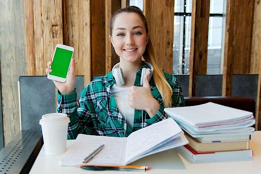 young girl studying at desk with iphone on lockdown